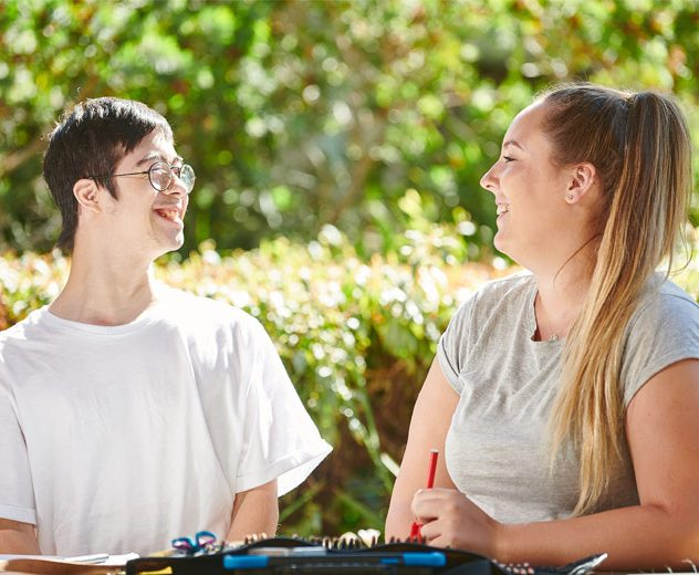 Smiling mentor and young man sitting at desk outside