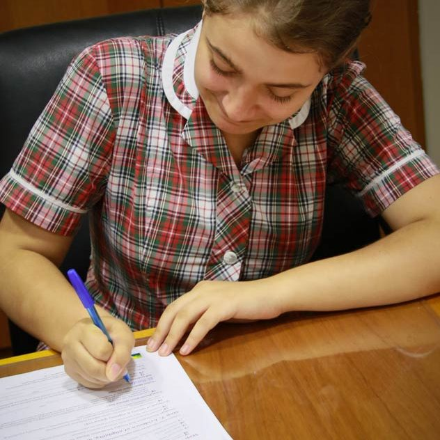 School girl writing on a piece of paper